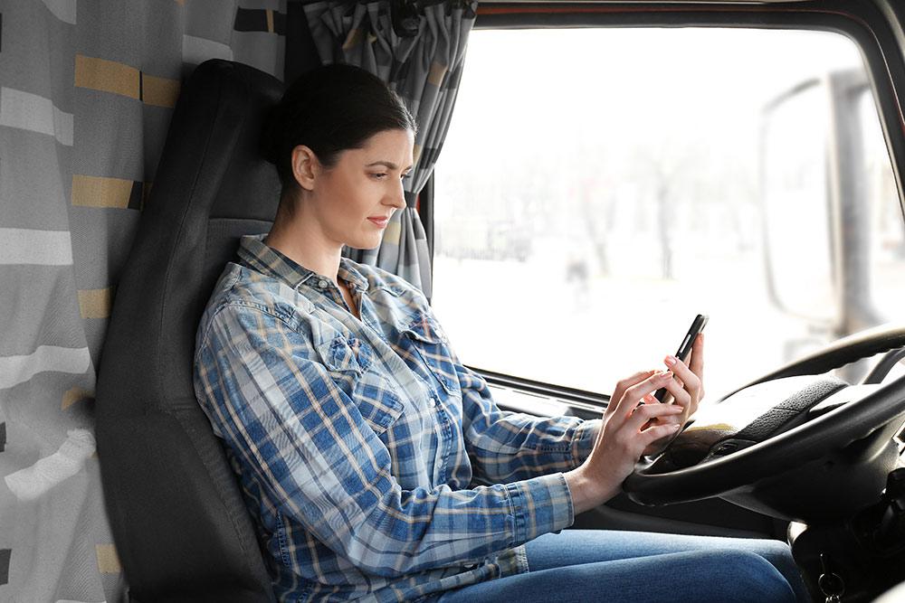 Woman, trucker on smartphone in truck cab