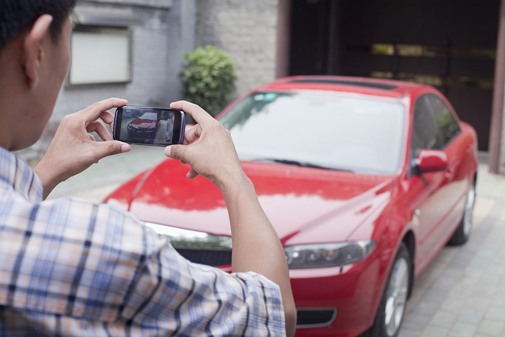 Man on smartphone taking picture of car