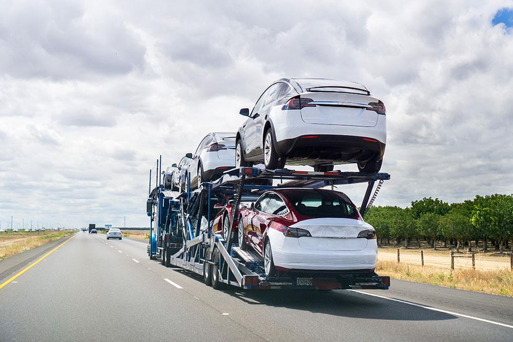 Semi truck driving down highway hauling cars, auto shipper