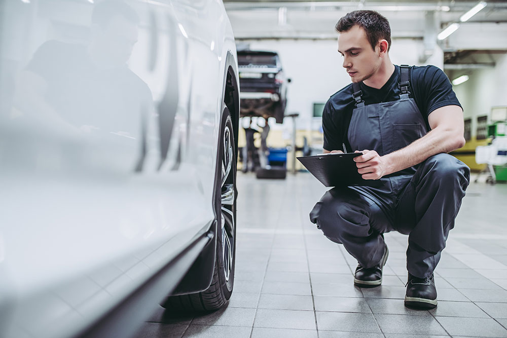 Man bent down next to car, inspecting car and writing on clipboard